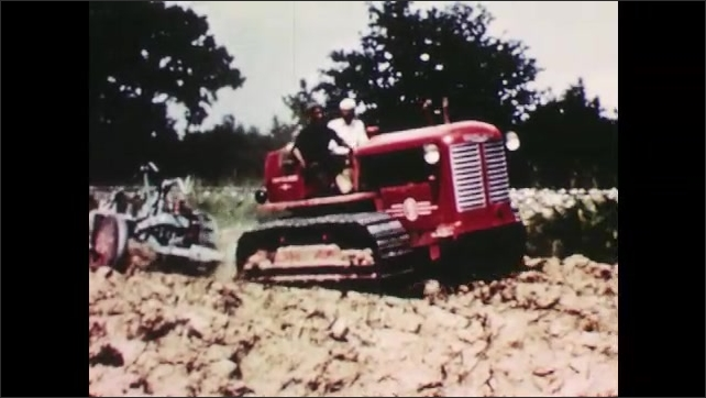 1950s: ITALY: EUROPE: tractor in field. Man ploughs field. Machine churns up soil.