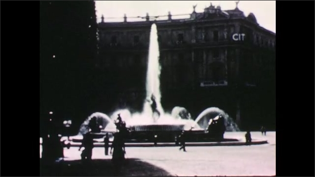 1950s: ITALY: EUROPE: fountain in Rome. Car drives in Rome. Cars drive in street