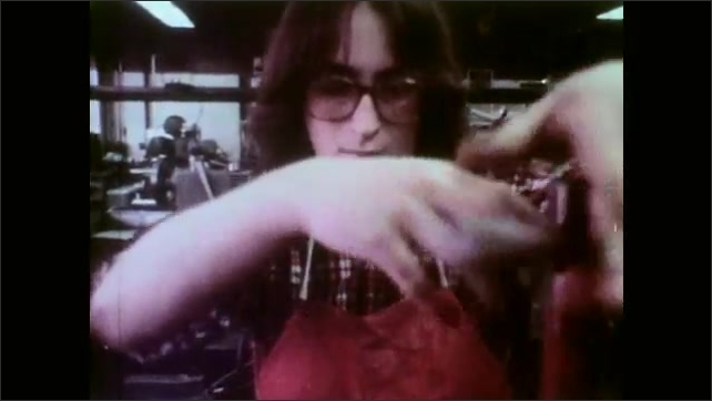 1970s: Girls wash hands and talk at basin. Girl in apron tightens bolts on machinery in workshop. Hands pull down lever. Girl operates die cutting machine in shop.