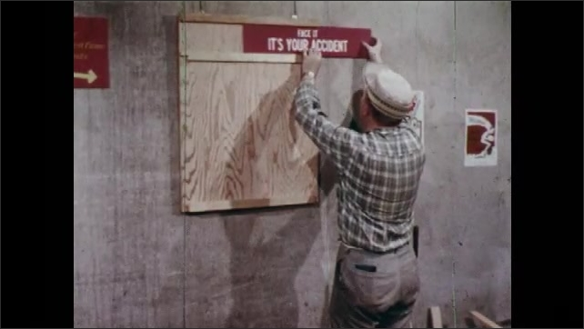 "1960s: Man finishes hanging board on wall and puts hammer in his pocket. He puts a title board reading ""Face it: It's Your Accident"". Man greets fellow workers."