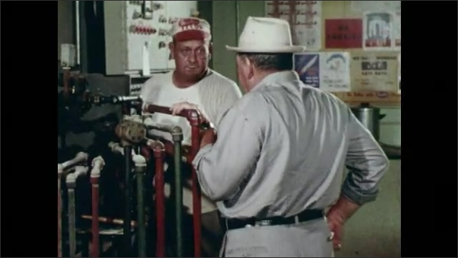 1960s: Driver exits the car and enters work. Plant foreman talks with worker near pipes.