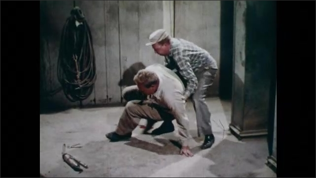 1960s: A man helps a man who lays on the floor. A man lifts injured man from the floor, holds him by the shoulders, calls for help, they walk away slowly. A room with blood on the ground.