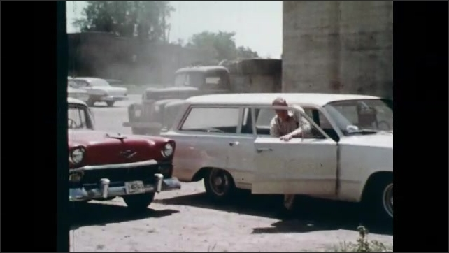 """1960s: Man forces car door open.  Man checks engine.  Parking lot.  Men talk.  Man gestures at sign that reads """"FACE IT.  IT'S YOUR ACCIDENT.""""  Man walks away."""