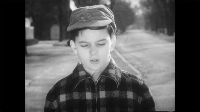 1940s: Group of kids dismiss boy, wave at him, walk away. Boy watches longingly as group walks away, boy turns around, walks down sidewalk, jumps on ledge.