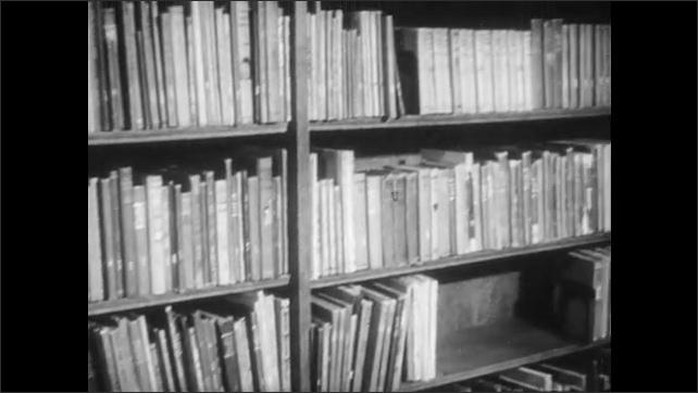 1940s: Boy hands books to woman behind desk, woman talks, gestures at books. Woman opens book, removes card, boy walks around desk, looks at card.