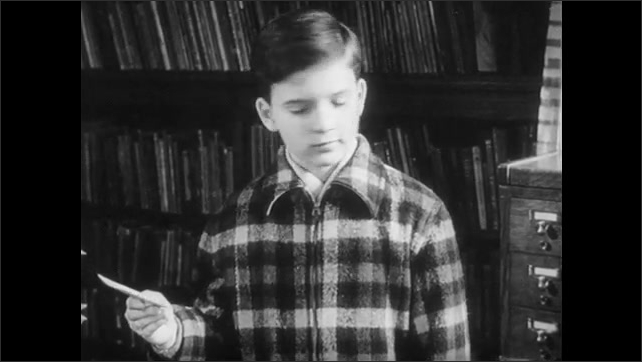 1940s: Woman sits at desk, boy stands by desk, woman hands card to boy, talks to boy. Boy takes card, talks, smiles, walks away. Woman moves books to side of desk. Boy exits library.