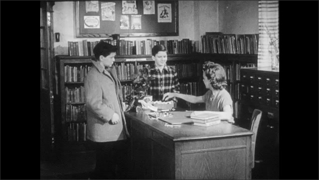 1940s: Boys walk up to librarian, boy removes hat, hands card to woman. Woman sits at desk, writes on card, boys watch.