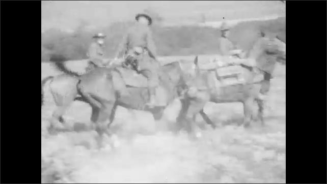 1920s: Men in uniforms ride horses fast across land, passed men sitting still on horses. Horse bucks with man riding it. Men ride horses running across land.