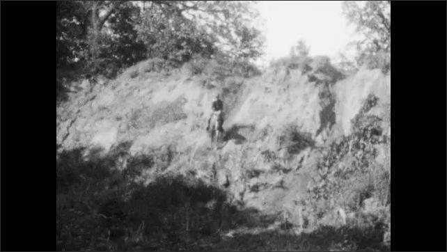 1920s: Man rides horse down steep dirt slope. Two men ride horses down steep dirt slopes. Man rides horse down steep dirt slope. Man holds piglet up by leg.
