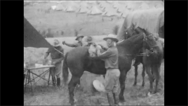 1920s: Men in uniforms stand around horses, talking. Man in overcoat addresses men in uniforms. Men at camp. Men in uniforms walk down sides of road with horses.