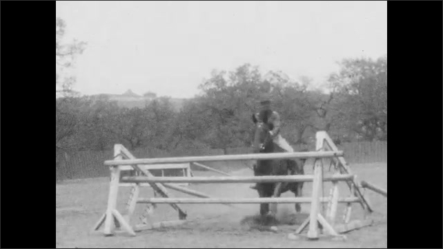 1920s: Man in uniform rides, jumps horse over hurdle. Man jumps horse over hurdle, horse knocks down hurdle. Man rides horse into hurdle. Man jumps horse over hurdle. Man jumps horse through hurdle.