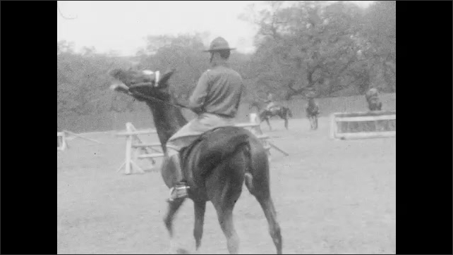 1920s: Man in uniform rides horse back and forth on obstacle course.