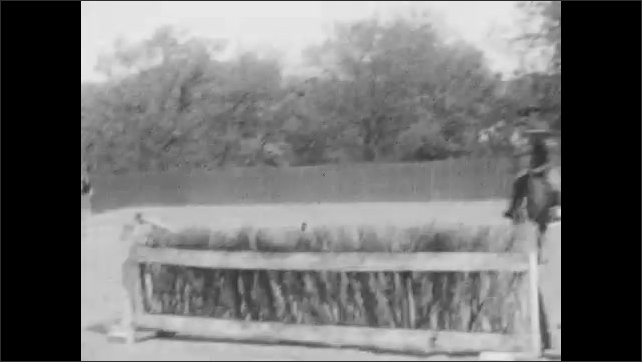 1920s: Men in uniforms jump horses consecutively over hurdles on obstacle course. Men jump horses over hurdle.