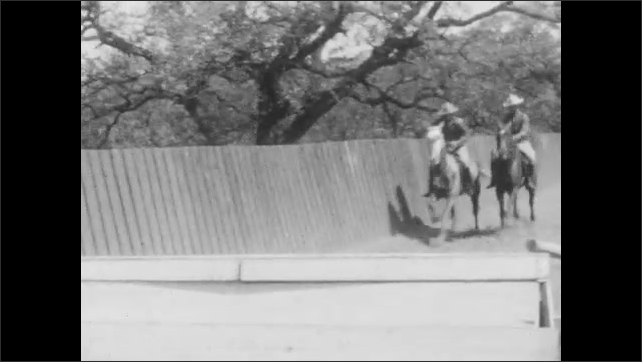 1920s: Men in uniforms jump horses consecutively over hurdles on obstacle course.