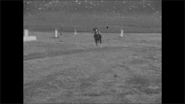 1920s: Men in uniforms ride horses through obstacle course, using swords to slice objects on pedestals.