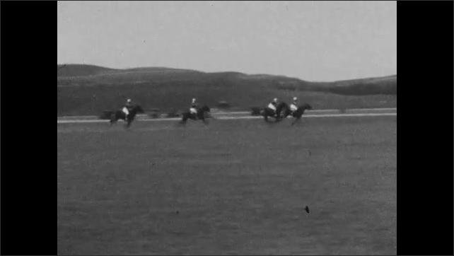 1920s: People race horses across track. People watching. People run horses over field.
