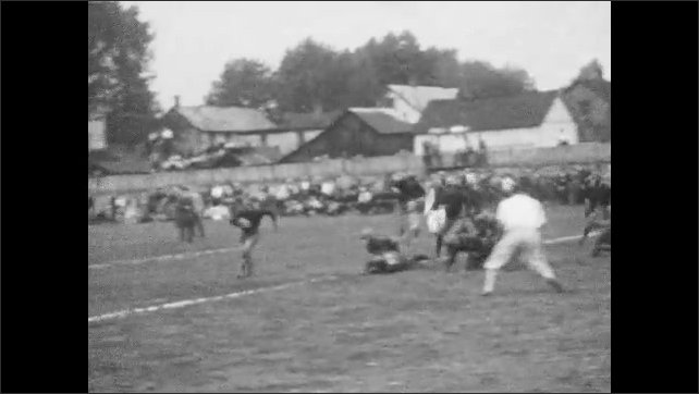 1920s: Football game.  Player runs with ball and gets tackled.  Players lean down for the snap.