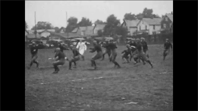 1920s: Football game.  Player kicks ball.  Young men run.