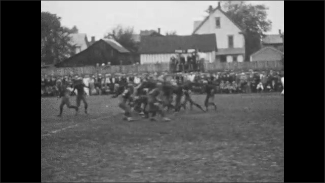 1920s: Football game.  Players run and tackle.