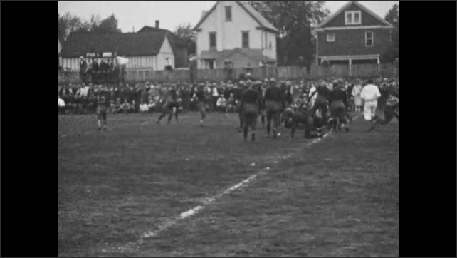 1920s: Football game.  Players run and tackle.  Young man brings water pail to players.