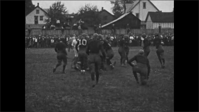 1920s: Football game.  Men run and tackle.