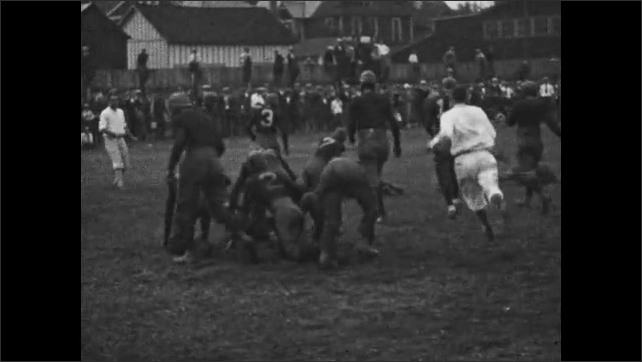 1920s: Referees.  Players in huddle.  Football game.  Men run and tackle.  Player runs with ball and falls.