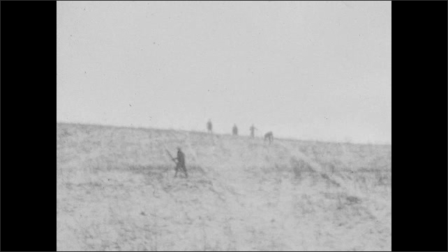 1920s: Person skis down snowy hill passed person standing still. Person skis partway down hill, stops then continues skiing down hill.