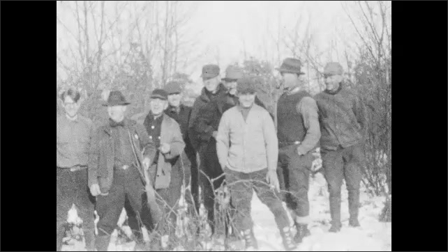 1920s: men in coats, boots, hats stand in snow, one has broom, one has pipe, man with cigar joins them, men start pulling, pushing, pretending to fight, men wrestle, man lifts other man's leg