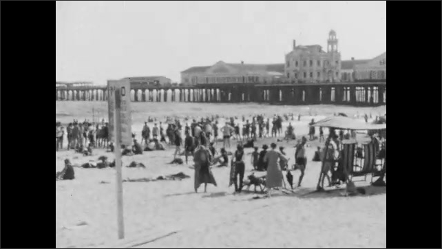 1920s: children, women and men walk along oceanfront boardwalk, crowd of beachgoers sit, stand, walk and run on beach as waves hit shore in background