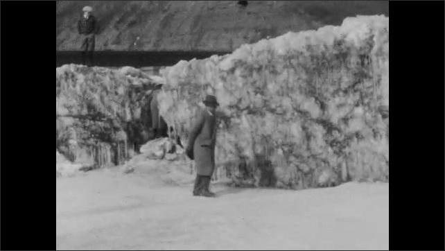 1920s: Hills, steam powered car drives by billowing steam. Snowy field, people stand, walk amongst snow covered boulders.
