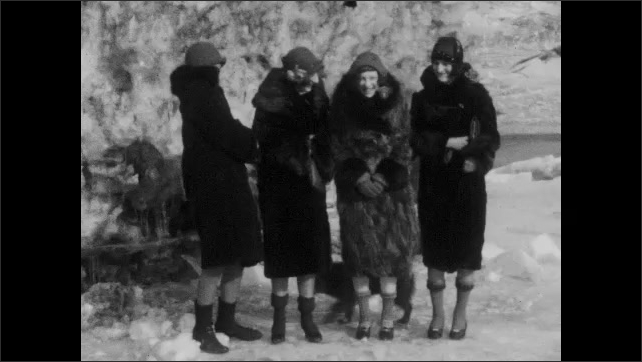 1920s: Snowy field, excited dog runs, bucks, wags tail, jumps, spins, does play bow. Women stand in hats, fur coats, shiver, hold coats tightly. Men stand on boulder, raise hats.