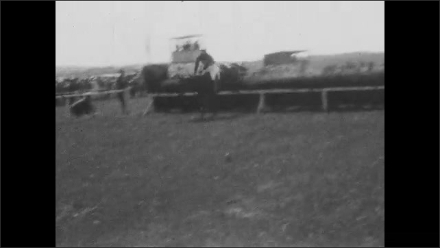 1920s: Men race on horses, jumping over hedge obstacle on track. Men race horses on track. Men in uniforms.