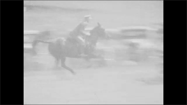 1920s: Men race on horses, jumping over hedge obstacle on track. Men race horses on track.