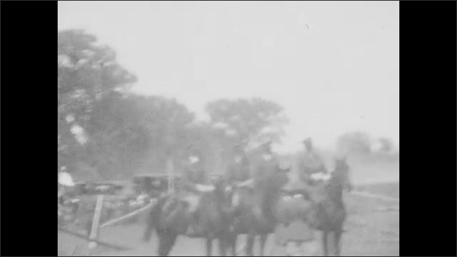 1920s: Man rides horse over obstacle course. Men in uniforms sit on horses. Man in uniform rides horse through obstacle course.