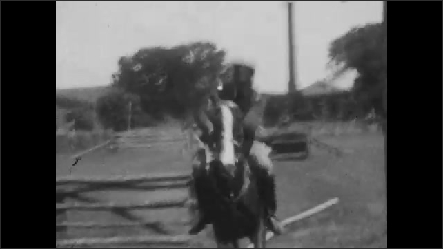 1920s: Man in uniform rides horses, jumping over hurdles on obstacle course. Man rides horse up to hurdles and stops. Men in uniforms sitting on horses. Man gives awards to men on horses.