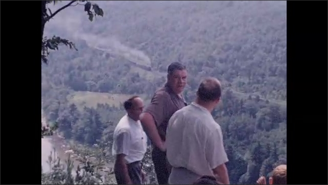 1940s: Group of people descend forest trail to scenic overlook; locomotive train passes by in valley.
