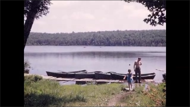 1940s: Views of wooded shore and homes from passing boat; young girl walks away from boat at lakeside; large group of vacationers descend steps of resort building.