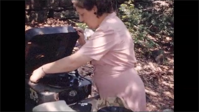 1940s: Vacationers approach large black sedans in parking lot; woman cranks portable record player, plays record.