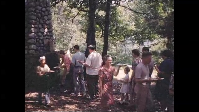 1940s: Man serves food from large outdoor grill; guests help themselves to picnic foods.