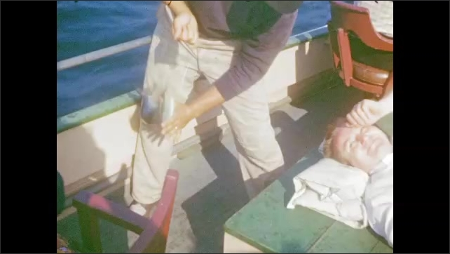 1940's: Fishermen assist tourists strapped into fishing chairs on back of boat; fish flaps on hook.
