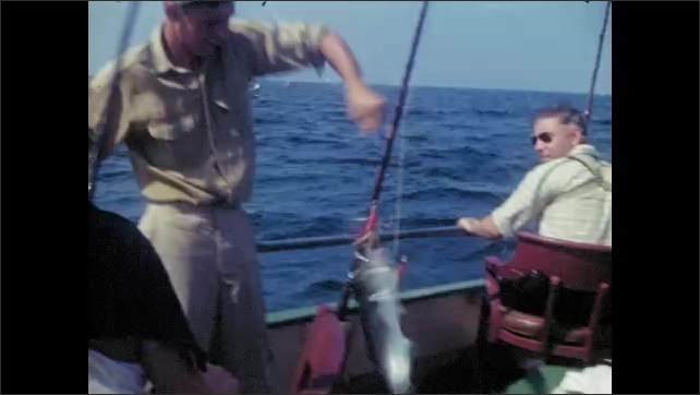 1940's: Blonde woman works at reeling in fish with large rod and reel, fisherman hauls in large fish; elderly man works fishing rod.