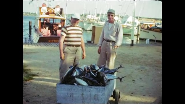 1940's: Freshly caught fish laid out on dock; men examine wagon full of fresh fish; man in raincoat fishes with rod off back of boat.