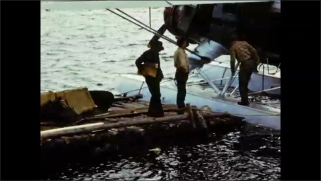 1940's: Men in seaplane cockpit; aerial views of mountain lakes, forest; plane parked at dockside as men disembark.