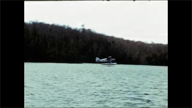1940's: Men chop firewood at campsite; seaplane lands on lake.