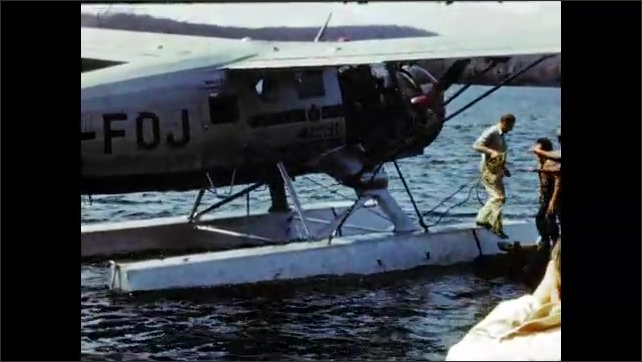 1940's: Seaplane taxis to dock on lake; men disembark.