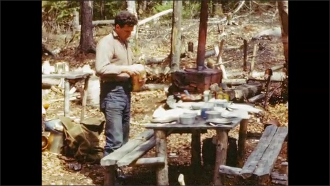 1940's: Man holds freshly caught trout; fish fillets are lowered into frying pan on outdoor stove.