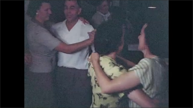 1940s: Nicely dressed men and women socialize, dance in living room.