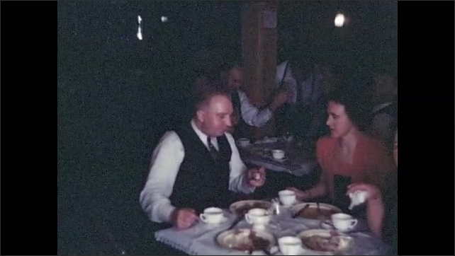 1940s: Nicely dressed guests eat at small tables in living room.