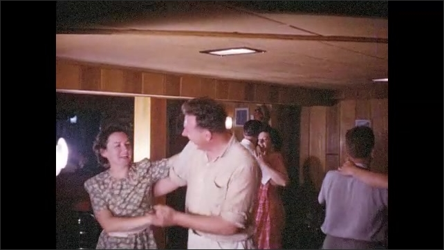 1940s: Couples dance cheerfully in basement party room.