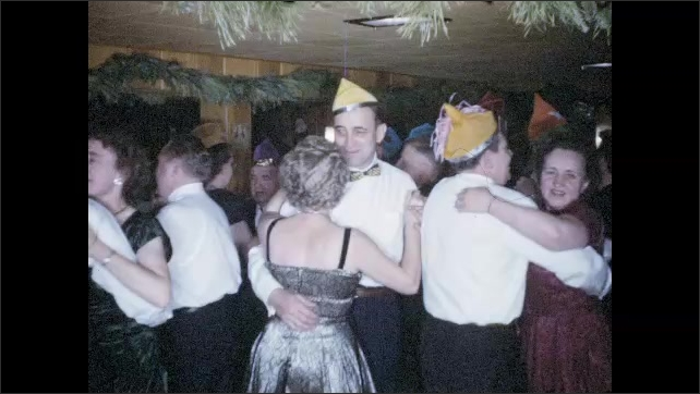 1940s:   Couples in colorful party hats dance at seasonal party in wood-paneled room.